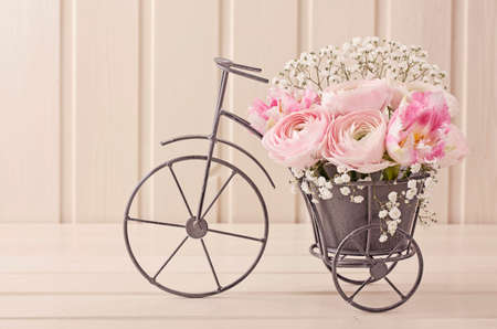 bikes: Ranunculus flowers in a bicycle vase