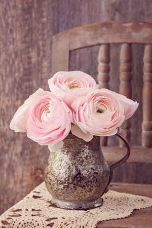 Ranunculus flowers in a old vase photo