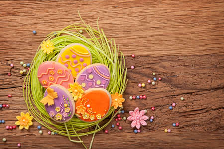 Colorful easter cookies on a wooden background photo