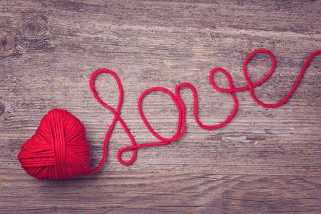 carta de amor: Coraz�n rojo de hilo de lana roja sobre madera