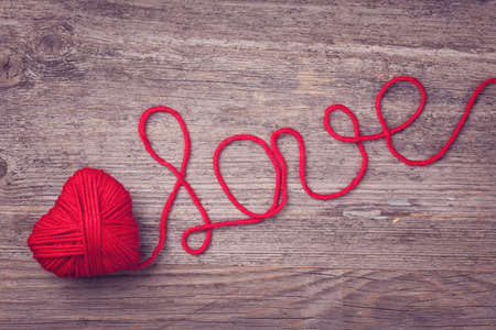 Red heart of red wool yarn on a wooden  photo