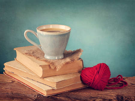Cup of coffee standing on old books and wool heart photo