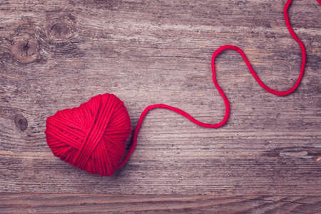 Red heart of red wool yarn on a wooden background photo