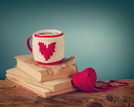 Cup of coffee standing on an old book and wool heart photo