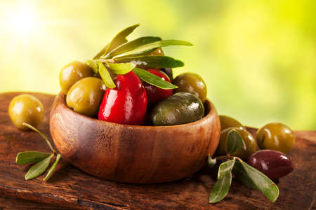 Bowl with mixed olives on a wooden table photo