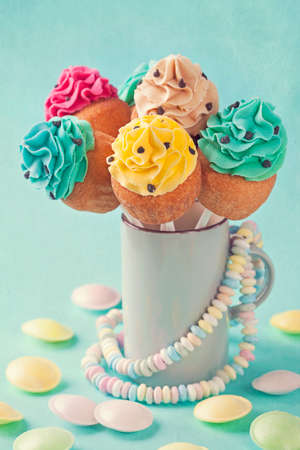 Colorful cupcake pops on blue background photo