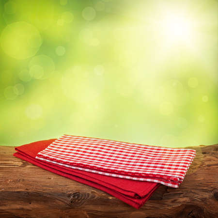 Empty wooden table with red napkins over green background photo