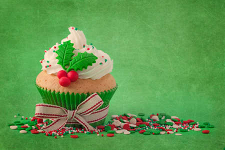Christmas cup cakes with holly berry on a green background photo
