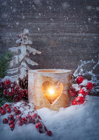 Winter candle on a wooden background photo