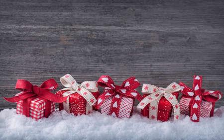 mo�os de navidad: Cajas de regalo rojos en la nieve Foto de archivo