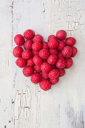 Heart from raspberries on a vintage wooden background