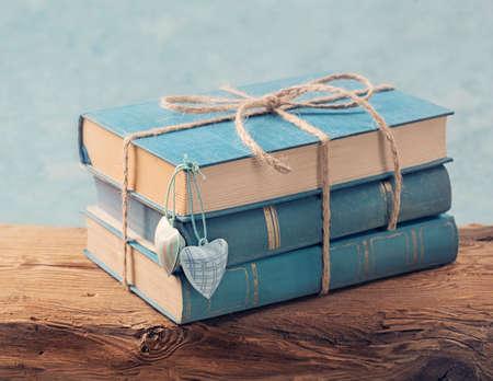 apilar: Pila de libros azules viejos en una mesa de madera Foto de archivo