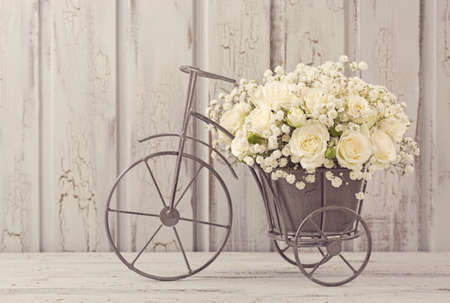 White roses in a bicycle vase Фото со стока