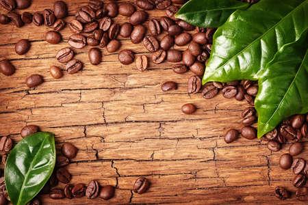 hojas antiguas: Los granos de café y hojas verdes sobre fondo de madera
