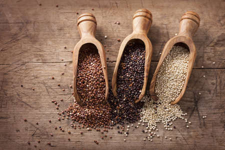 Red, black and white quinoa seeds on a wooden background