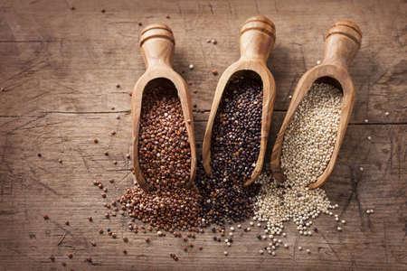 Rouge, noir et blanc graines de quinoa sur un fond de bois