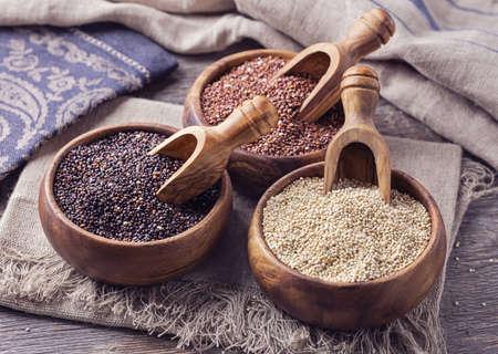 Rood, zwart en wit quinoa zaden op een houten achtergrond