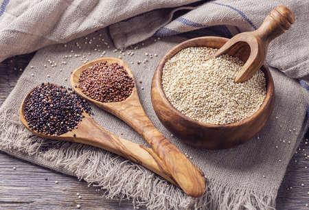Rood, zwart en wit quinoa zaden op een witte achtergrond