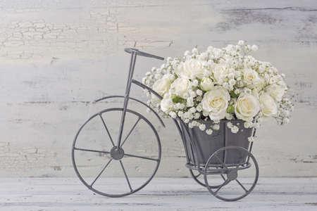 rosas blancas: Rosas blancas en un jarrón de bicicletas