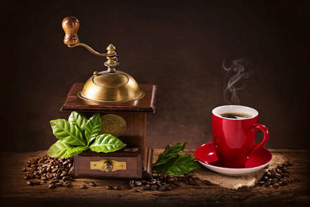food still: Coffee mill with beans and green leaves and a cup of coffee Stock Photo
