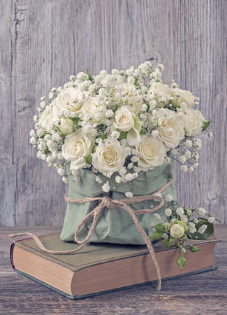 White roses and a book over wooden background