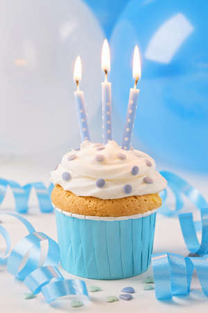Blue cup cake with birthday candles and balloons