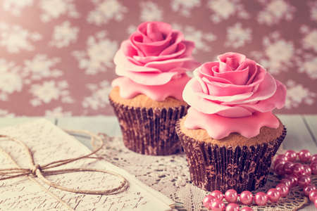 cup cakes: Cupcakes with sweet rose flowers and a letter Stock Photo