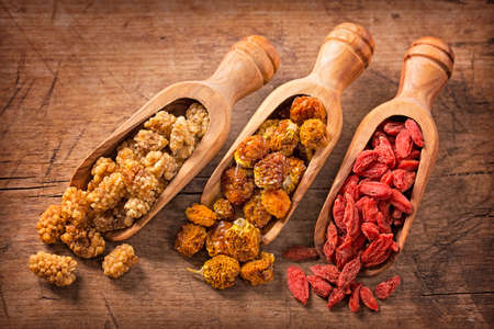 berry: Dried mulberries, physalies and goji berries on a wood background