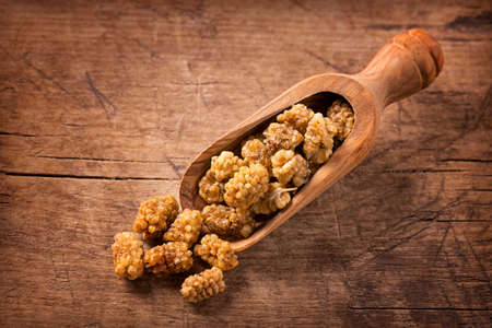 superfruit: Mulberries in a spoon on a wooden background