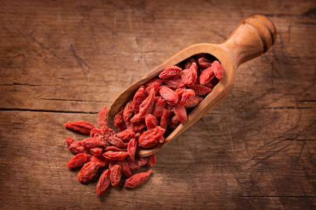 barbarum: Goji berries in a spoon on a wooden background Stock Photo