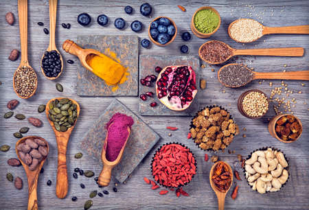 acai: Super foods in spoons and bowls on a wooden background