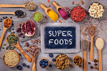 cuchara: Súper alimentos en cucharas y tazones de fuente en un fondo de madera Foto de archivo