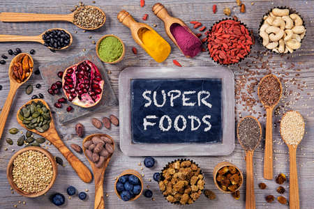 dry powder: Super foods in spoons and bowls on a wooden background