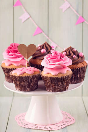 sweets: Cupcakes with sweet rose flowers and a cakepick for text
