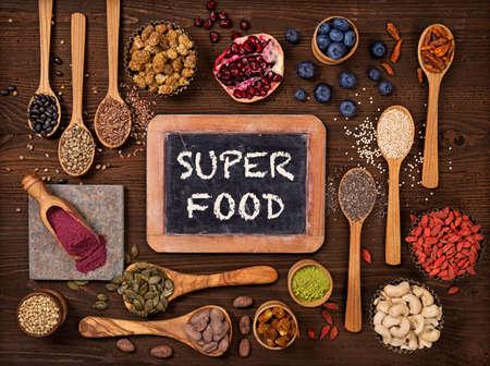 Super żywność w łyżki i miski na drewnianym tle