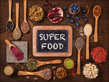 Super foods in spoons and bowls on a wooden background