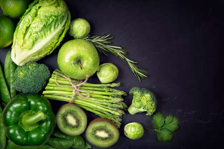 Green healphy vegetables and fruits on a black slates Foto de archivo