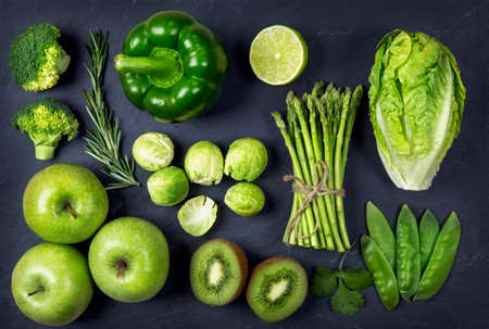 Green healphy vegetables and fruits on a black slates Standard-Bild
