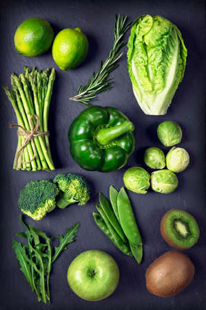 Green healphy vegetables and fruits on a black slates Archivio Fotografico