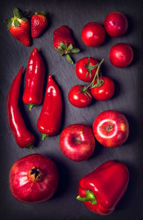 Red healphy vegetables and fruits on a black slates