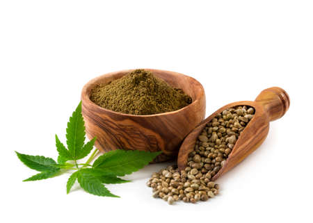 Hemp seeds and flour with a green leaf on a white background Standard-Bild
