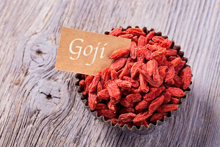lycium: Goji berries in a bowl on a wooden background