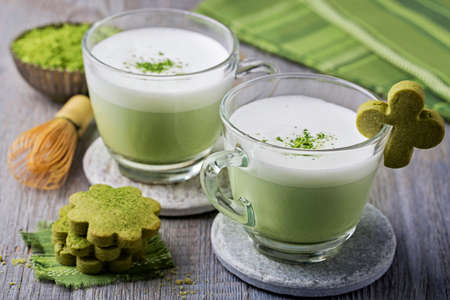matcha: Green tea latte and cookies on a wooden background