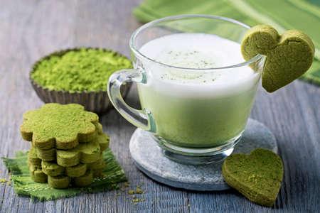 Matcha groene thee latte en koekjes op een houten achtergrond