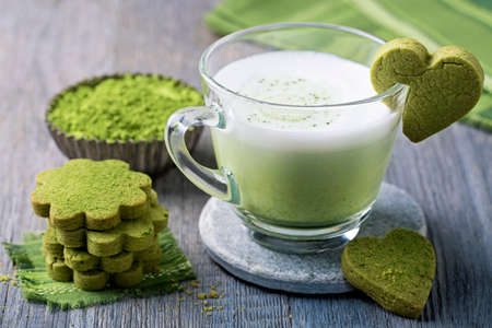 Matcha green tea latte and cookies on a wooden background