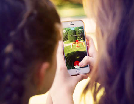 go: Vienna, AUSTRIA - August 1, 2016: Little girls playing a Pokemon Go game outdoors. Pokemon Go is a location-based augmented reality mobile game.