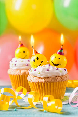 Cupcakes with smiley candles and colorful balloons