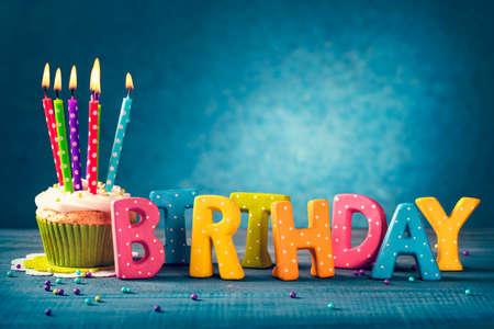 Magdalena con las velas de cumpleaños sobre un fondo azul