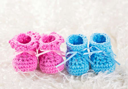 baby blue: Pink and blue baby crochet shoes on a white fur