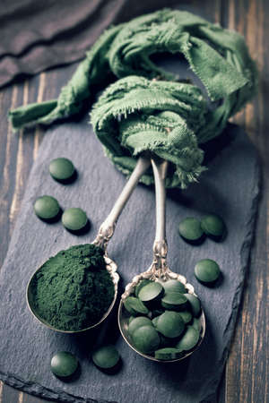 spirulina: Spoons with spirulina pills and powder